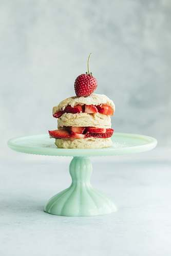 fruit cake with strawberries on teal ceramic cake stand plant