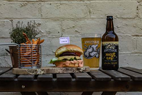 photo burger hamburger on chopping board by basket of fries and beer bottle alcohol free for commercial use images