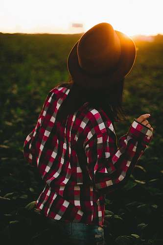 apparel woman wearing hat and checked shirt on green grass clothing