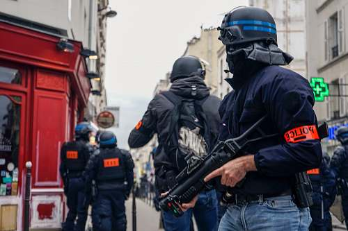 person Police wearing black helmets and holding guns apparel