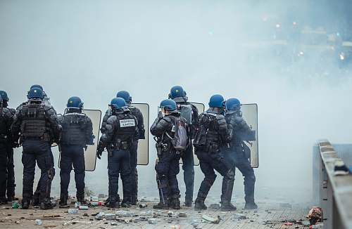 person riot police holding shield in front of smoke apparel