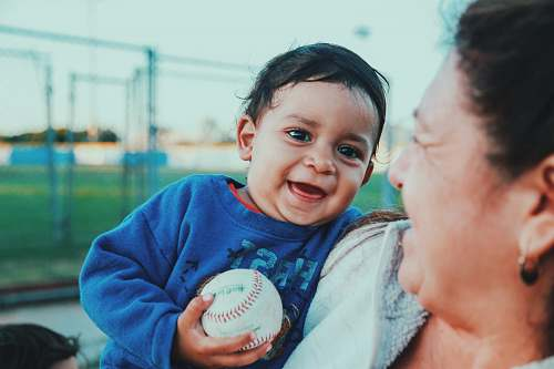 person selective focus photo of baby holding baseball baseball