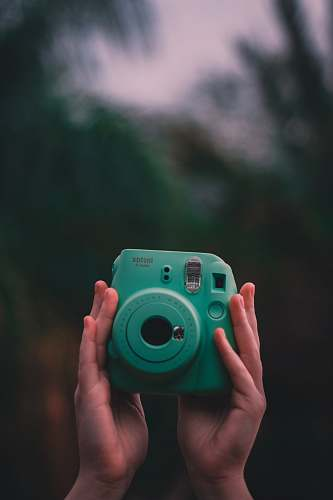photo electronics selective focus photo of person holding teal Fujifilm Instax instant camera camera free for commercial use images