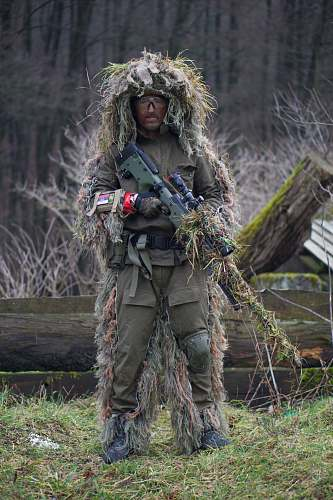 sniper soldier covered with grass holding sniper rifle military