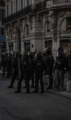 person soldiers holding shields near building black-and-white