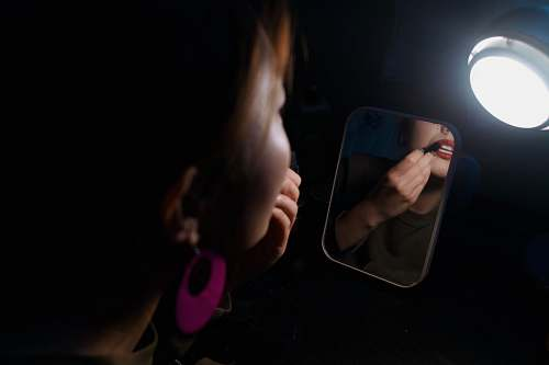 photo person woman facing the mirror putting lipstick on the lips hand free for commercial use images