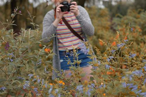 person woman holding camera standing beside flowers during daytime camera