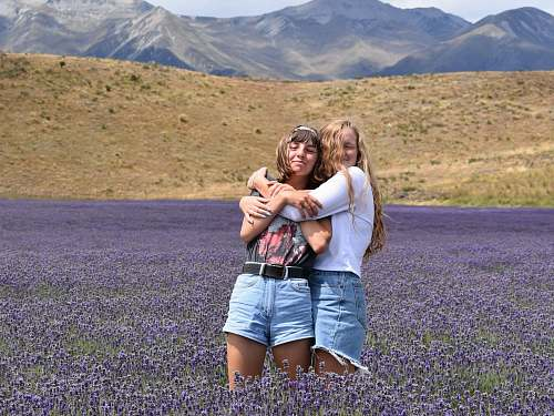 person woman hugging another woman on purple flower field people