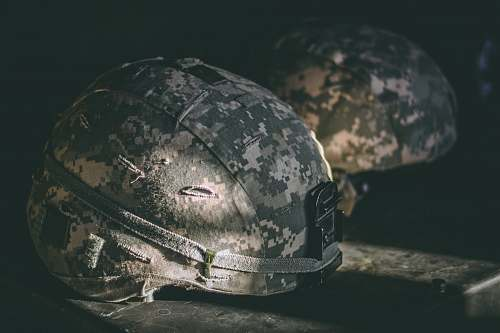hat gray and brown camouflage nutshell helmet on table grey