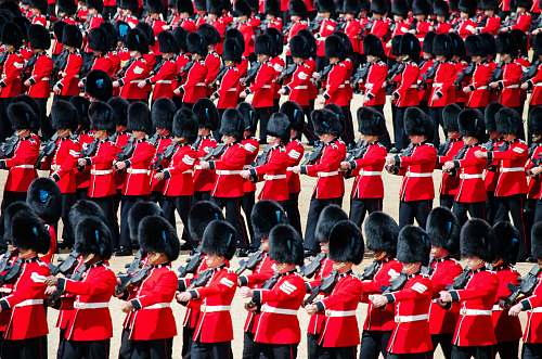 army men in red uniform playing instrument marching