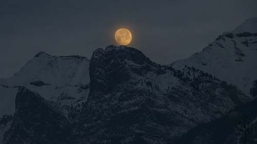 outdoors full moon over a snowy mountain top night