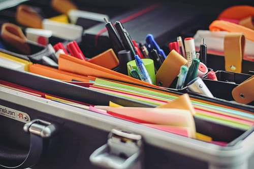 work assorted pen and colored papers in organizer case stationery