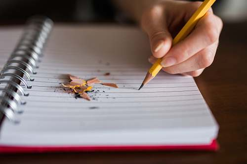 writing person holding pencil writing on notebook notebook