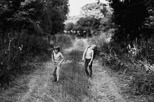 human boy and girl on footpath between grass grayscale photography black-and-white