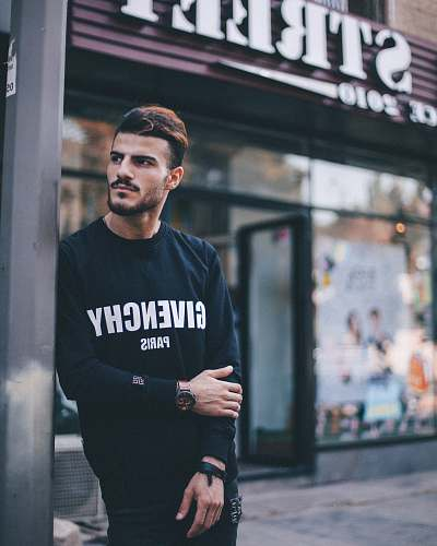 person man in black Givenchy sweatshirt standing beside of post in front of Strek store during daytime shallow focus photography human