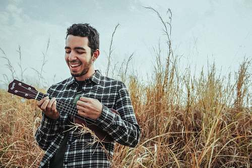 person man playing ukulele while standing on grass field human