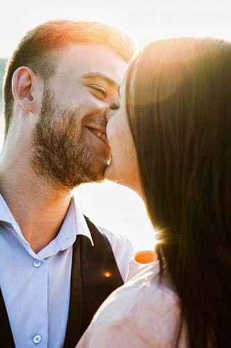 photo person smiling coupe kissing with sun rays during daytime human free for commercial use images