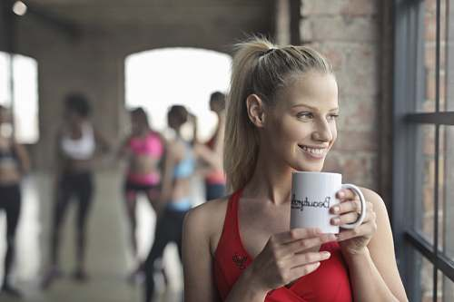 person woman holding white ceramic mug while smiling near glass window human