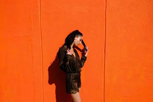 person woman near orange wall human