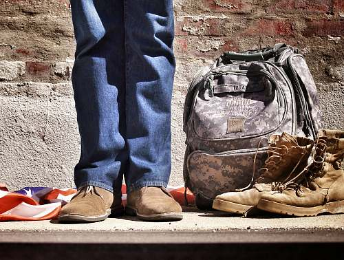 footwear minimalist photography of person standing near backpack and boots shoe