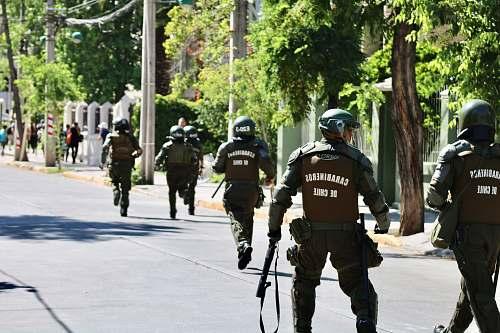 human running and walking men in police uniform holding rifles during daytime apparel