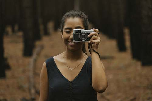 human woman holding silver DSLR camera during daytime people