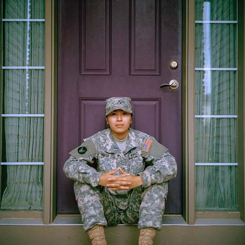 military woman sitting in front of closed door door