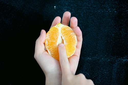 food person holding sliced orange fruit fruit
