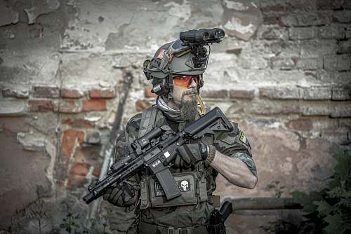 weaponry soldier man holding assault rifle while standing near building gun