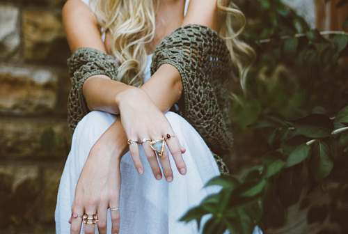 fashion woman sitting beside plant and concrete wall jewelry