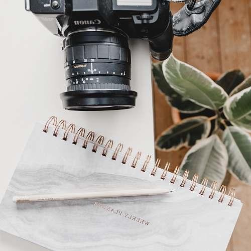 electronics black Canon DSLR camera on table beside notebook footwear