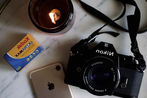 photo candle black Nikon DSLR camera on white table fire free for commercial use images