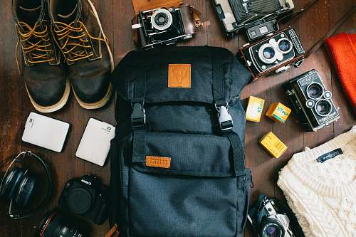 electronics high-angle photo of black bag beside cameras, portable HDD and black leather lace-up boots flatlay