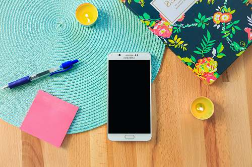 phone white Samsung Galaxy smartphone on top of blue place mat near blue click pen samsung