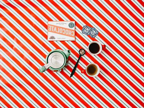hole cup of coffee on red and white striped surface flat aly
