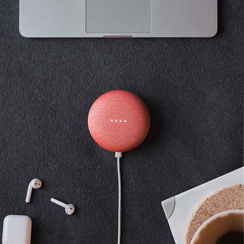 tech flat lay photography of coral Google Home Mini on black surface beside Apple AirPods cincinnati