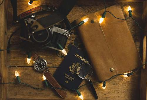 brown passport and SLR camera on table with string lights lights
