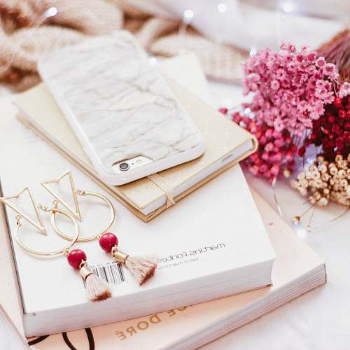 pink iPhone on book beside gold-colored earrings girly