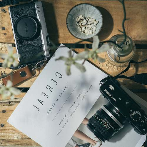 camera white printer paper between two black DSLR cameras cereal