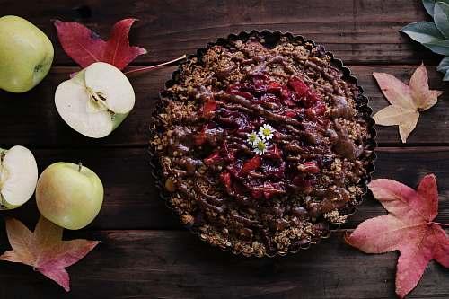 leaf baked pastry on brown wooden surface beside sliced apples cake