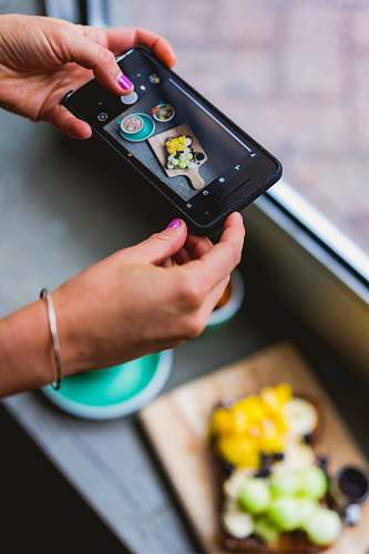 phone person taking photo of food cell phone