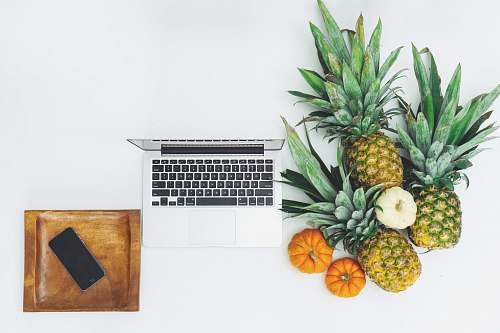 pineapple pineapple fruits near MacBook on white surface food
