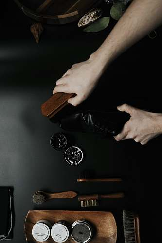 person brown and black brush shoe care
