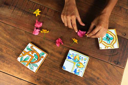 gambling person holding pink flower petal on brown parquet floor game