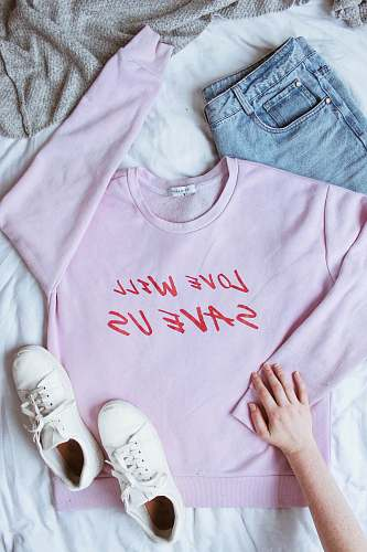 human pink long-sleeved shirt on white textile near white low-top sneakers and blue denim bottoms people