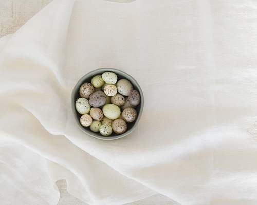 food pebbles in gray ceramic bowl on white textile produce