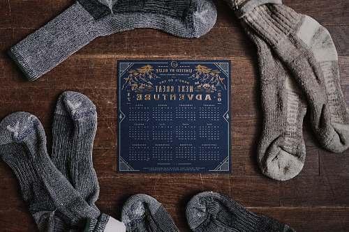 knitting pair of gray socks and blue calendar on table socks