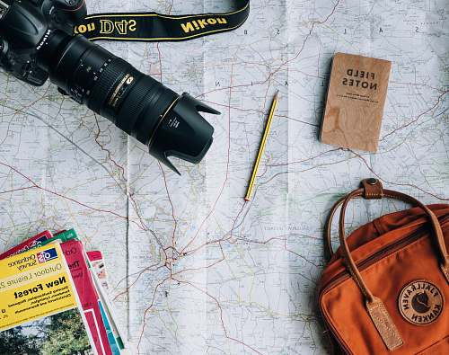 pencil flat lay photography of camera, book, and bag notebook