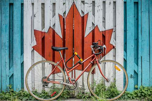 photo canada red road bike beside red and white wooden maple leaf painted wall bike free for commercial use images