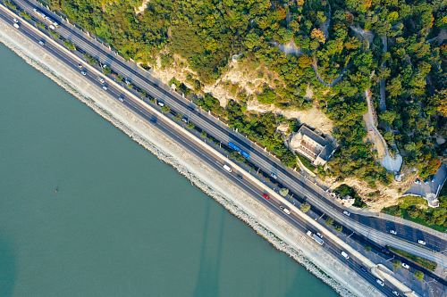 aerial photography of highway between body of water and mountain during daytime